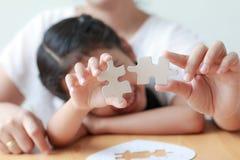 Asiatisk liten flicka som spelar pusslet med hennes moder för fami royaltyfri foto