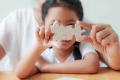 Asiatisk liten flicka som spelar pusslet med hennes moder för fami fotografering för bildbyråer