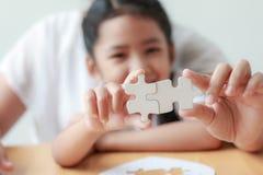 Asiatisk liten flicka som spelar pusslet med hennes moder för fami arkivfoton