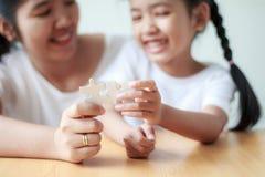 Asiatisk liten flicka som spelar pusslet med hennes moder för fami arkivfoto