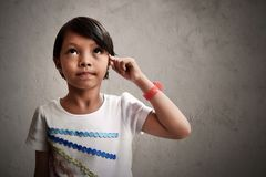 Asiatisk liten flicka som tänker på väggbakgrunder Arkivbild