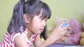 Asiatisk liten flickalekvideospel i vardagsrum arkivfilmer