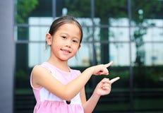 Asiatisk liten flickast?lling som pekar hennes pekfinger bredvid med gulligt leende royaltyfria bilder
