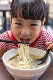 Asiatisk liten kinesisk flicka som äter nudelsoppa Arkivbild