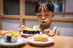 Asiatisk liten kinesisk flicka som äter sushi royaltyfri foto