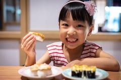 Asiatisk liten kinesisk flicka som äter sushi fotografering för bildbyråer
