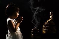 Asiatisk liten kinesisk flicka som framme ber av Buddha royaltyfri bild
