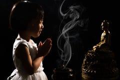 Asiatisk liten kinesisk flicka som framme ber av Buddha arkivbilder
