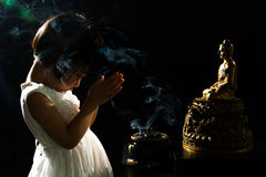 Asiatisk liten kinesisk flicka som framme ber av Buddha royaltyfria bilder