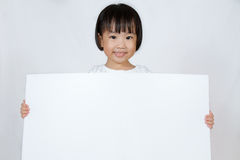 Asiatisk liten kinesisk flicka som rymmer ett vitt mellanrum Royaltyfri Fotografi