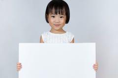 Asiatisk liten kinesisk flicka som rymmer ett vitt mellanrum Royaltyfria Foton