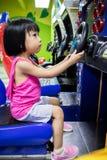Asiatisk liten kinesisk flicka som spelar Arcade Game Machine Arkivbild