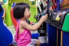 Asiatisk liten kinesisk flicka som spelar Arcade Game Machine Arkivbilder