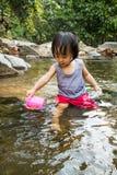 Asiatisk liten kinesisk flicka som spelar i liten vik Arkivfoto