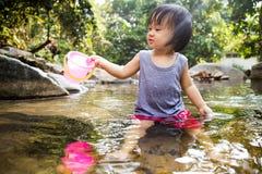 Asiatisk liten kinesisk flicka som spelar i liten vik Arkivfoton