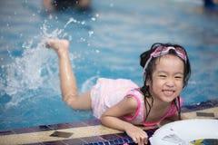 Asiatisk liten kinesisk flicka som spelar i simbassäng Royaltyfri Bild