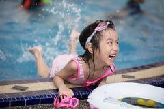 Asiatisk liten kinesisk flicka som spelar i simbassäng Fotografering för Bildbyråer