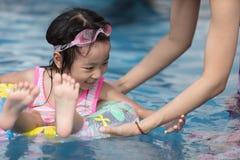 Asiatisk liten kinesisk flicka som spelar i simbassäng Royaltyfri Fotografi