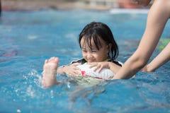 Asiatisk liten kinesisk flicka som spelar i simbassäng Royaltyfria Foton
