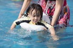 Asiatisk liten kinesisk flicka som spelar i simbassäng Royaltyfria Bilder