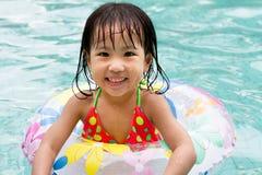 Asiatisk liten kinesisk flicka som spelar i simbassäng Arkivfoto