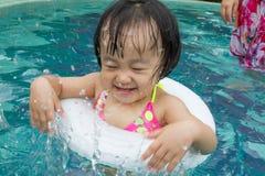 Asiatisk liten kinesisk flicka som spelar i simbassäng Arkivfoton