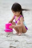 Asiatisk liten kinesisk flicka som spelar sand med strandleksaker Royaltyfri Foto