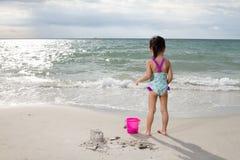 Asiatisk liten kinesisk flicka som spelar sand med strandleksaker Royaltyfri Bild