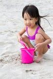 Asiatisk liten kinesisk flicka som spelar sand med strandleksaker royaltyfria foton