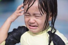 Asiatisk liten kinesisk flickagråt i simbassäng Fotografering för Bildbyråer