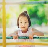 Asiatisk liten unge som spelar i nöjesfältet Arkivbild