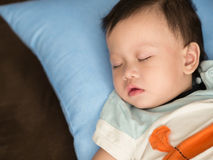 Asiatisk litet barnavverkning in i en slummer på säng Royaltyfria Bilder