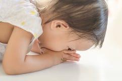 Asiatisk litet barnflicka som är nedbruten själv till fläderna för tack Royaltyfria Bilder