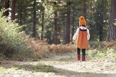 Asiatisk litet barnflicka som bara går i en skog, baksidasikt arkivfoton
