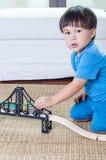 Asiatisk litet barnpojke som spelar med en drevuppsättning. Royaltyfri Foto