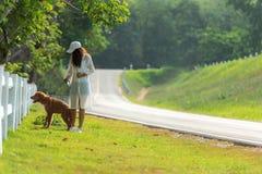 Asiatisk livsstilkvinna som går så lyckligt med golden retrieverkamratskaphunden nära vägen fotografering för bildbyråer