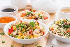 Asiatisk lunch - stekt ris med tofuen, nudlar med grönsaker royaltyfri bild