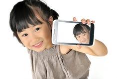 Asiatisk lycklig liten flicka som tar selfie vid den isolerade mobiltelefonen Arkivbild