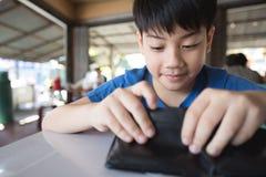 Asiatisk lycklig pojke med plånboken arkivbild