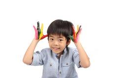 Asiatisk lycklig pojke som ler med färgrika händer Fotografering för Bildbyråer