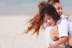 Asiatisk mamma och son som spelar på stranden Arkivfoton