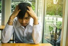 Asiatisk man för affär för sammanträde eller för kanal för affärsman som ledsen sitter ch royaltyfria bilder