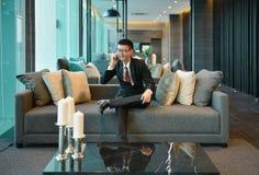 Asiatisk man för affär som använder en smartphone på soffan i lyxig andelsfastighet fotografering för bildbyråer