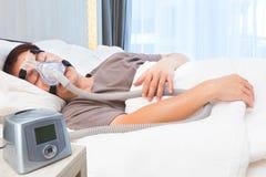 Asiatisk man för mellersta ålder som sover den bärande CPAP-maskeringen som förbinder till ai Royaltyfri Bild