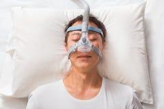 Asiatisk man för mellersta ålder som sover i hans säng som bär CPAP-maskeringsconne Arkivbilder