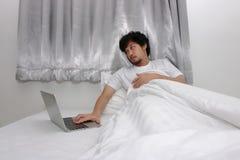 Asiatisk man för trött indolens som arbetar på bärbara datorn på sängen i sovrum fotografering för bildbyråer