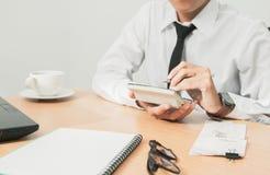 Asiatisk man i den vita skjortainnehavpennan som skriver en skattrapportledning till likvideringen och använder räknemaskinen arkivbilder