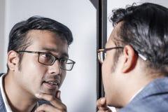 Asiatisk man i dräkt som framme sköter hans utseende av en spegelskönhet som utformar livsstil royaltyfria bilder