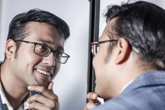 Asiatisk man i dräkt som framme sköter hans utseende av en spegelskönhet som utformar livsstil royaltyfria foton