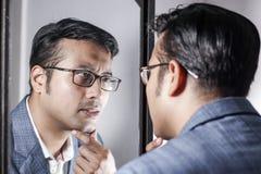 Asiatisk man i dräkt som framme sköter hans utseende av en spegelskönhet som utformar livsstil royaltyfri foto